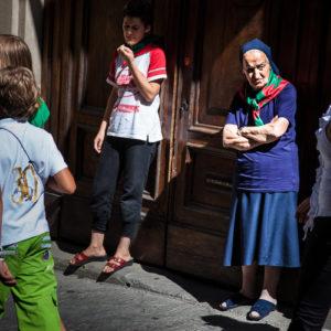 Una suora assiste alla processione con i colori del proprio quartiere al collo (Arezzo 2009)