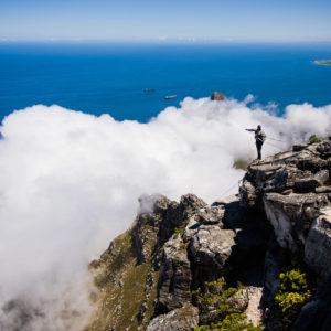 Uno scalatore si accinge a scendere dalla cima di Table mountain. In alto a destra Robben Island, nella cui prigione Nelson Mandela è stato imprigionato per 18 anni (Città del Capo, Sudafrica 2009)