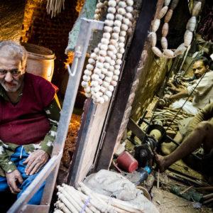 Un uomo mastica paan accanto ad una bottega dove si lavora al tornio a Old Delhi (India 2012)