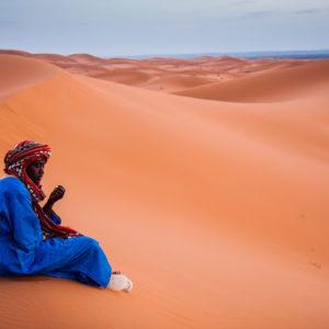 Dopo aver accompagnato tutto il giorno decine di turisti, un giovane cammelliere berbero si concede un attimo di malinconico riposo davanti al tramonto (Merzouga, Marocco, 2010)