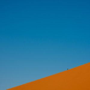 Un fotografo scende da un'alta duna dopo aver raggiunto la cima per ammirare l'alba sul deserto (Merzouga, Marocco, 2010)